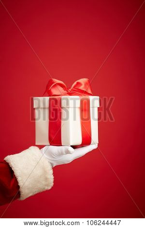 Giftbox bound with red ribbon on Santa palm