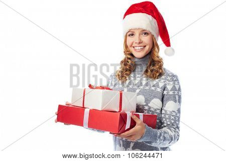 Happy girl in sweater and Santa cap holding giftboxes