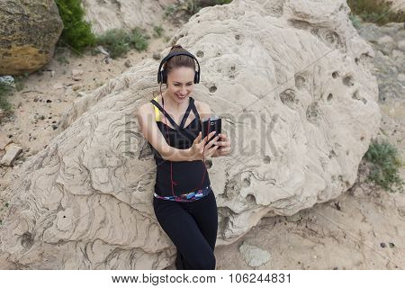 Half length portrait of sport girl making self portrait with mobile phone camera