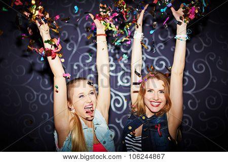 Two ecstatic girls having fun in night club
