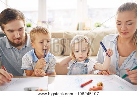 Modern family with crayons drawing together