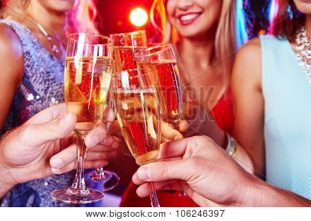 Group of friends clinking with flutes of champagne at party
