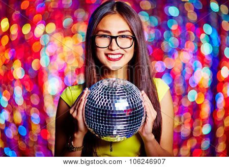 Posh female with toothy smile holding disco ball