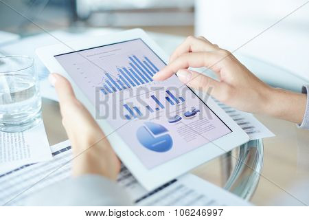 Businesswoman using touchpad while analyzing data