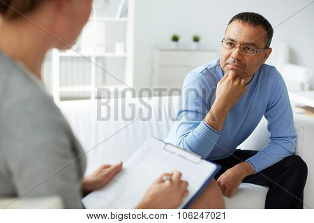 Pensive man in eyeglasses listening to psychologist
