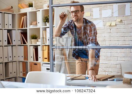 Young designer writing on glassy wall