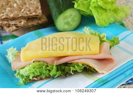 Crisp bread with ham, lettuce and cucumber on wooden board