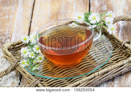 Chamomile tea with fresh chamomile flowers on wicker tray on rustic wooden surface with copy space