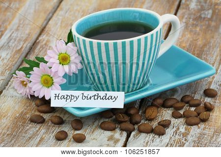 Happy birthday card with cup of coffee and pink daisies on rustic wooden surface