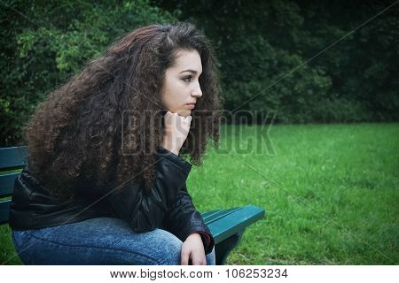 sad young woman sitting on bench