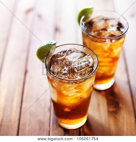 iced tea with lime wedges on wooden table and copy space composition