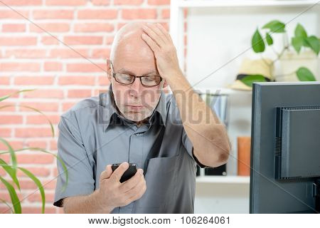an anxious man looks at his smartphone