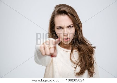 Portrait of a young angry woman pointing finger at camera isolated on a white background