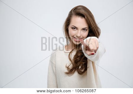 Portrait of a happy woman pointing finger at camera isolated on a white background