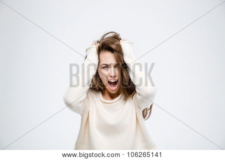 Portrait of a young woman screaming isolated on a white background