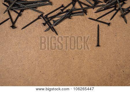 Wood screws on brown fibreboard