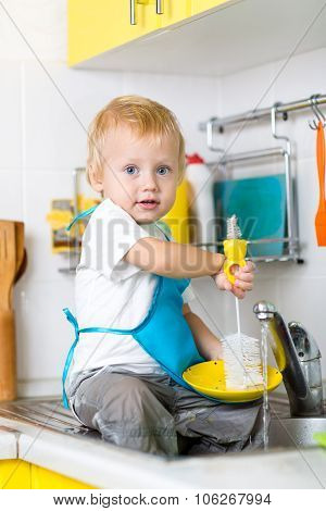Child boy washing dishes and having fun in the kitchen
