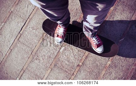 self-portrait of a young man wearing red sneakers on a skate board