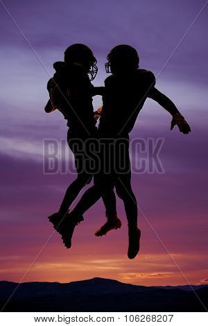 Silhouette Of Two Football Players Bumping Chests