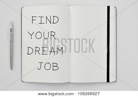 high-angle shot of a pen and a notepad with the text find your dream job written in it