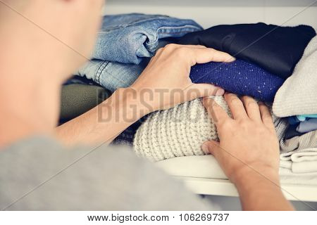 closeup of a young caucasian man arranging the closet