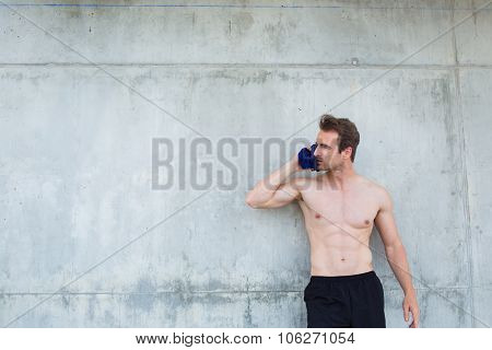 Portrait of a young fit men taking break between training outdoors