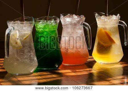 Multicolored soft drinks, lemonade in jugs. Wooden table background.