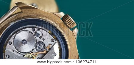Detailed view of ancient clock parts. dark green background.
