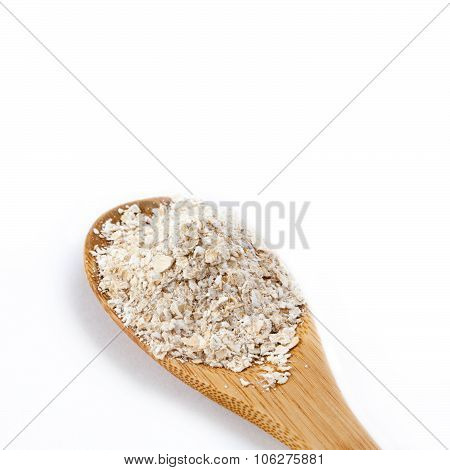 Wooden spoon with oat bran. Macro view. Isolated on white background