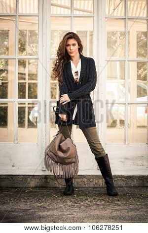 woman in worm dark wool sweater,  black leather high boots hold leather hand bag with tassels stand in front glass door, full body shot