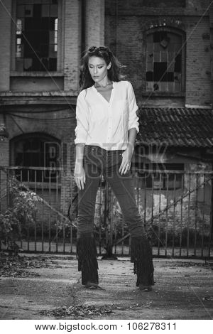 young woman in shirt,  tight pants and tassel boots, stand in front old building, black and white, full body shot