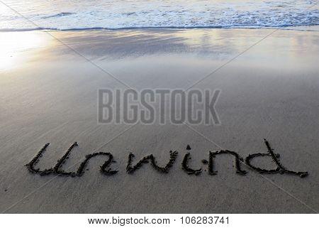 Unwind Written on the Beach