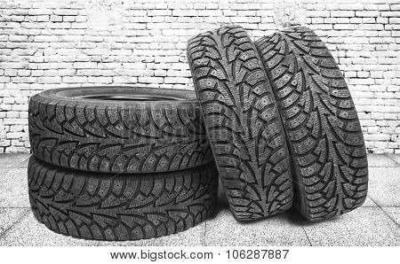 Stack of four new black tyres for winter car on  floor in vintage room with brick wall background