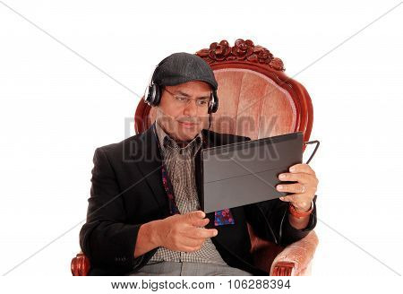 Man Listening From His Tablet.