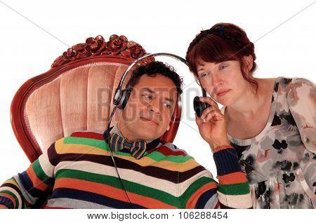 Husband And Wife Listening On Headphone.