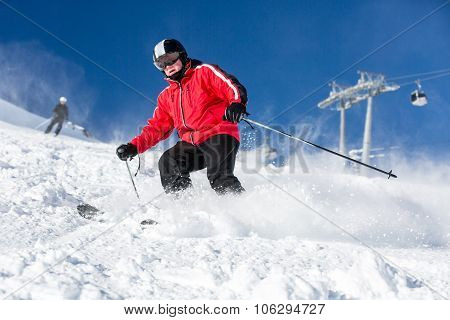 Male Skier Skiing At Ski Resort