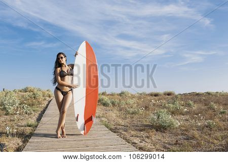 Young seductive women in swinsuit holding surfboard with copy space for your brand