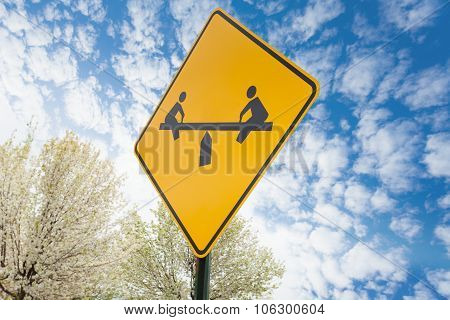 Teeter-totter yellow sign on sky background