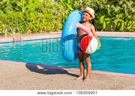 Small boy with inflatable ring, ball, pool noodle