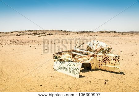 Car Wreck In The Namibian Desert - Danger Sign About Driving Off Roads