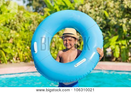 Boy in hat who holds inflatable ring near pool