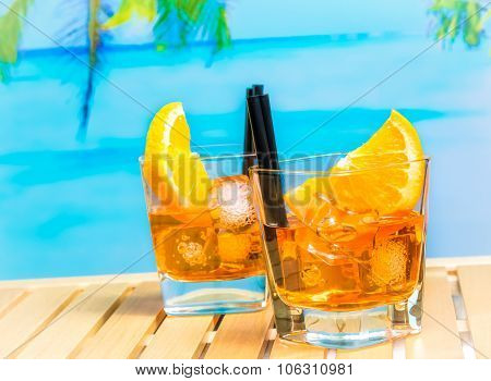 Two Glasses Of Spritz Aperitif Aperol Cocktail With Orange Slices And Ice Cubes On Blur Beach And Pa