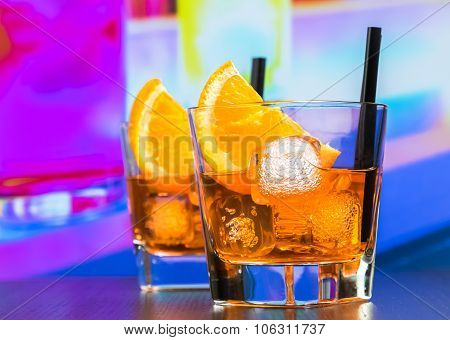 Two Glasses Of Spritz Aperitif Aperol Cocktail With Orange Slices And Ice Cubes On Bar Table, Disco