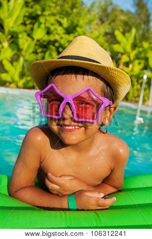 Cute boy in star-shaped sunglasses on green airbed