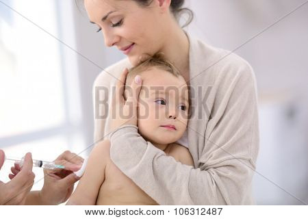 Baby girl at doctor's office receiving vaccine injection