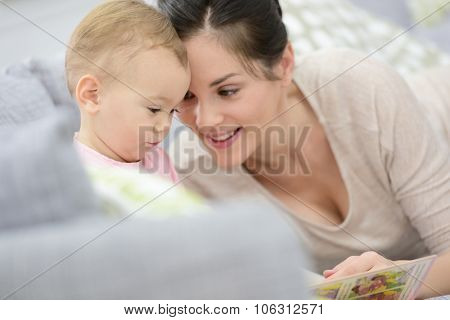 Mother and daughter reading book sitting in sofa