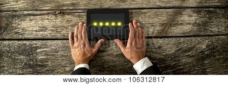 Top View Of Male Hand Holding Digital Tablet With Five Golden Stars Appearing On The Screen