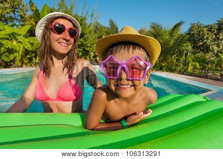 Happy mother and boy wearing funny sunglasses