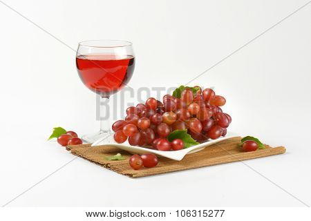 plate of ripe red grapes and glass of red wine on brown place mat