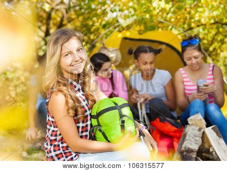 Happy girl holds green sleeping bag during camping